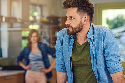 Buy stock photo Shot of a young man looking upset after a fight with his wife who is standing in the background