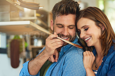 Buy stock photo Shot of a man giving his wife a taste of the food that he's preparing at home