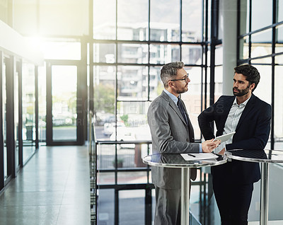 Buy stock photo Shot of two businessmen looking over a tablet in the office
