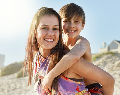 Buy stock photo Portrait of a mother giving her son a piggyback ride at the beach
