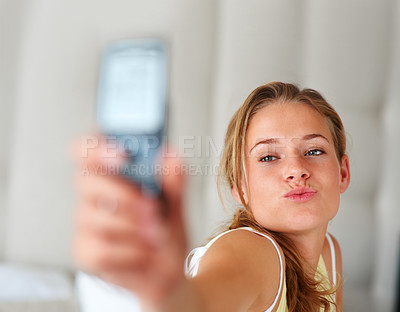 Buy stock photo Portrait of an attractive young woman taking picture of herself through her mobile phone