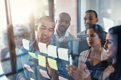 Buy stock photo High angle shot of a group of coworkers brainstorming on a glass wall