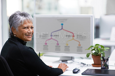 Buy stock photo Portrait of a happy mature businesswoman using her computer in the office