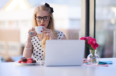 Buy stock photo Shot of a creative young businesswoman drinking coffee while using her laptop in the office