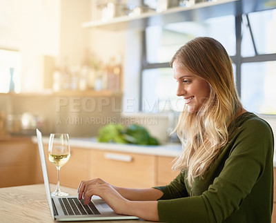 Buy stock photo Shot of an attractive young woman using laptop on her kitchen counter at home