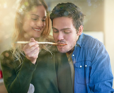 Buy stock photo Shot of an affectionate young couple tasting a sauce they are preparing together in their kitchen
