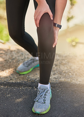 Buy stock photo Shot of an unrecognizable young woman holding her knee in pain during her morning run