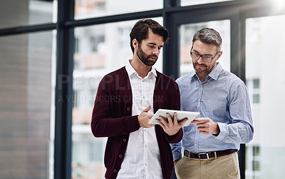 Buy stock photo Cropped shot of a businessman showing something to his colleague on his tablet in the office