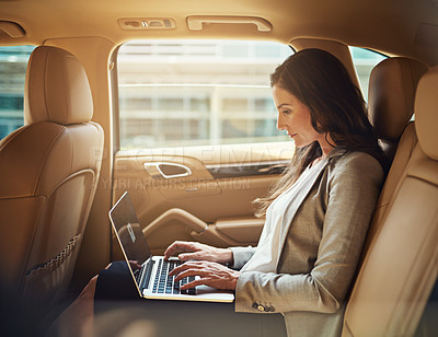 Buy stock photo Shot of a beautiful businesswoman working on her laptop while traveling in the back seat of a car