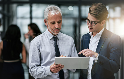 Buy stock photo Shot of two professional coworkers using a digital tablet together at work