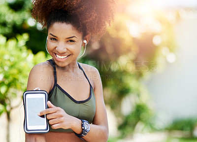 Buy stock photo Cropped shot of a young woman starting her playlist before her run
