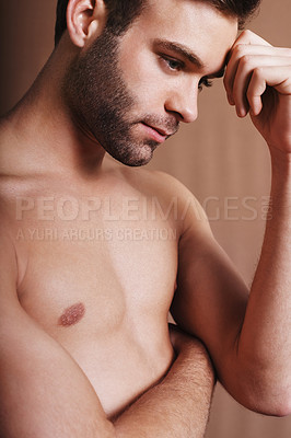 Buy stock photo Shot of a handsome and shirtless young man posing against a brown background