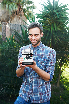 Buy stock photo Shot of a handsome young man taking photographs while out in nature