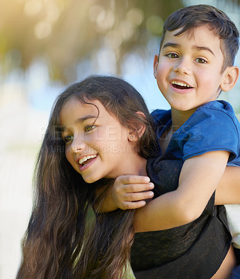 Buy stock photo Shot of a cute little girl giving her brother a piggyback ride at home