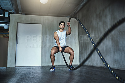 Buy stock photo Shot of a sporty young man working out with heavy ropes at the gym