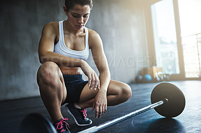 Buy stock photo Shot of a sporty young woman working out with a barbell at the gym