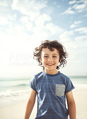 Buy stock photo Portrait of a happy little boy standing alone on the beach