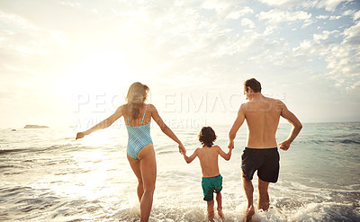 Buy stock photo Shot of two parents running hand in hand with their little son on the beach in the late afternoon