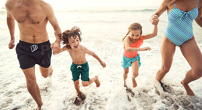 Buy stock photo Shot of two parents running hand in hand with their little children on the beach in the late afternoon