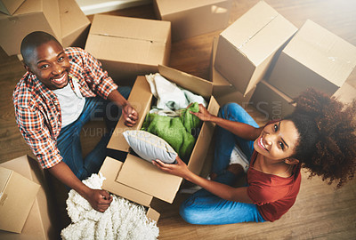 Buy stock photo Portrait of a young couple unpacking boxes while moving into their new home