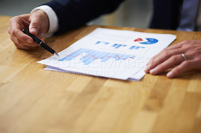 Buy stock photo Closeup shot of a businessman sitting at a table in an office going through graphs