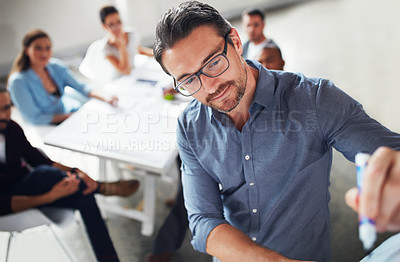 Buy stock photo Shot of a mature man writing on a whiteboard while giving a presentation to colleagues in an office