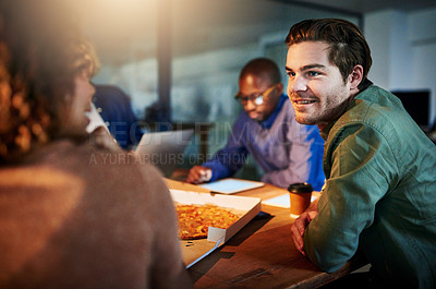 Buy stock photo Shot of a team of young businesspeople eating pizza while working late in the office