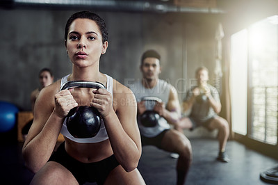 Buy stock photo Shot of a fit young woman working out with a kettle bell at the gym