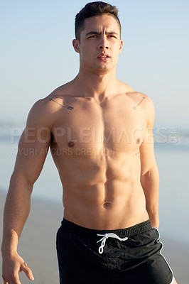 Buy stock photo Cropped shot of a handsome young man warming up before a workout on the beach