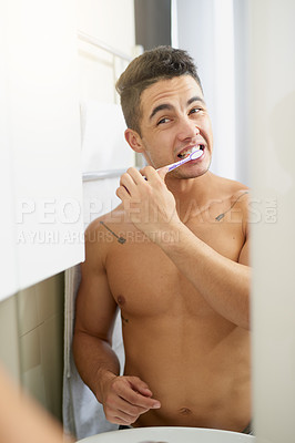 Buy stock photo Shot of a handsome young man brushing his teeth in his bathroom