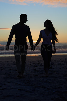 Buy stock photo Silhouette shot of a young couple walking on the beach