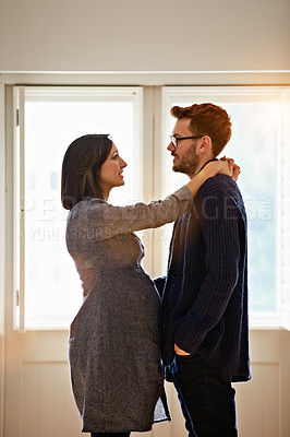 Buy stock photo Shot of a happy pregnant couple standing face to face together in their home