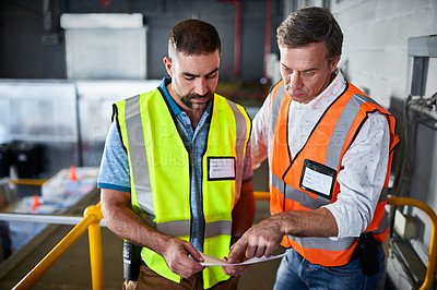 Buy stock photo Shot of two workers discussing paperwork while standing on stairs in a large warehouse