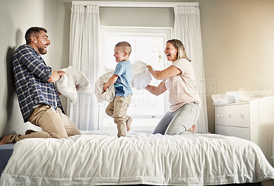 Buy stock photo Full length shot of a family of three pillow fighting on a bed at home