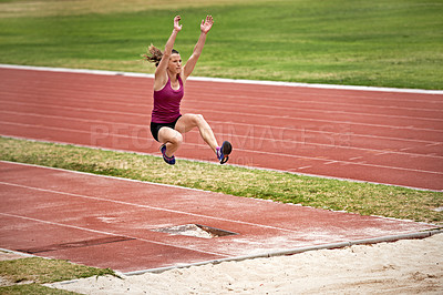 Buy stock photo Shot of a young woman in mid air doing a long jump on a sports field