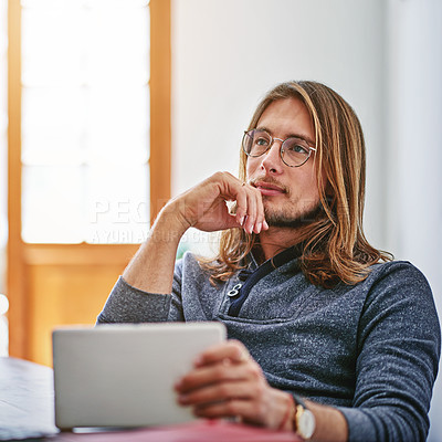 Buy stock photo Shot of a young man deep in thought while using a digital tablet at his desk in an office