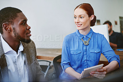 Buy stock photo Shot of two smiling colleagues talking together while while using a digital tablet in an office