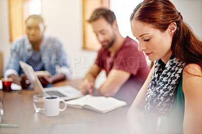 Buy stock photo Shot of a young woman sitting at a desk in an office with colleagues in the background
