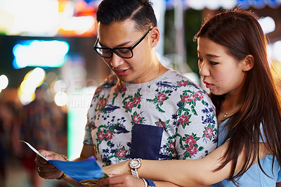 Buy stock photo Cropped shot of a young couple looking at a map while out in the city