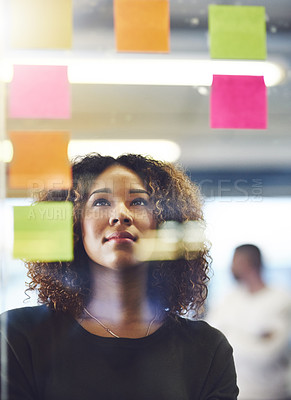 Buy stock photo Shot of a young woman having a brainstorming session with sticky notes at work