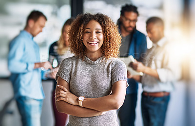 Buy stock photo Portrait of an attractive young designer standing in the office with her colleagues in the background