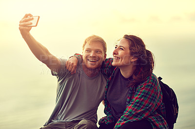 Buy stock photo Cropped shot of a young couple taking a selfie on a mountain top