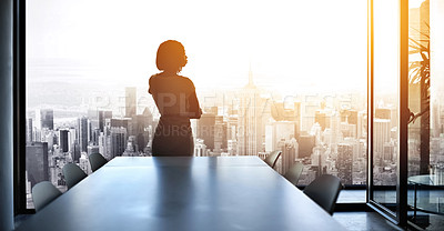 Buy stock photo Rearview shot of a young businesswoman looking out from a large window in the office
