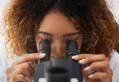 Buy stock photo Cropped shot of a young female scientist looking into a microscope