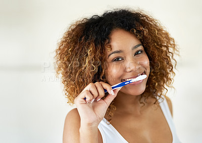 Buy stock photo Shot of a young woman brushing her teeth in her bathroom