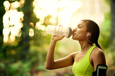 Buy stock photo Cropped shot of a young woman drinking water after her workout