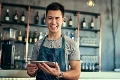 Buy stock photo Cropped portrait of a young man working on a tablet in his coffee shop