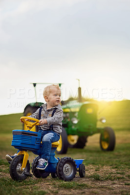 Buy stock photo Shot of an adorable little boy riding a toy truck on a farm