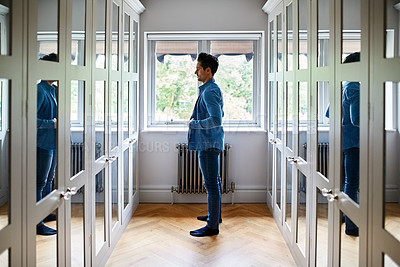 Buy stock photo Shot of a man getting dressed in a long walk in closet full of mirrors