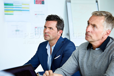 Buy stock photo Shot of two coworkers listening to a presentation druing a meeting in an office